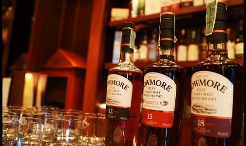 Three bottles of Bowmore whisky on a bar top with several whisky glasses beside them and blurred shelves filled whisky in the background.