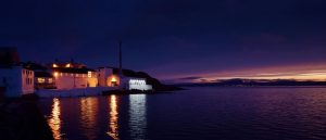 View of Bowmore whisky distillery from the water at sunset.